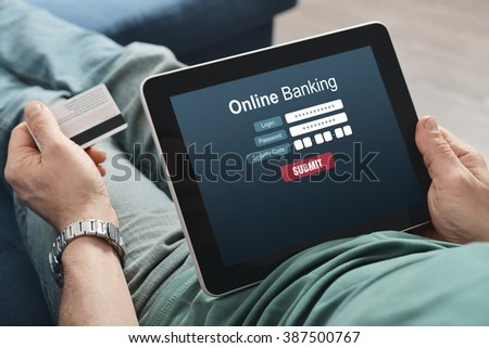 Male hands using online banking on touch screen device - stock photo