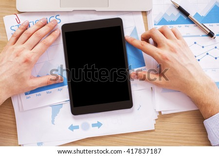 Male hands with black tablet on wooden desk with business report. Topview, Mock up - stock photo