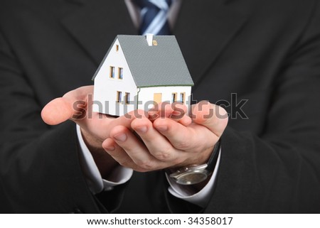 male hands with model of house - stock photo