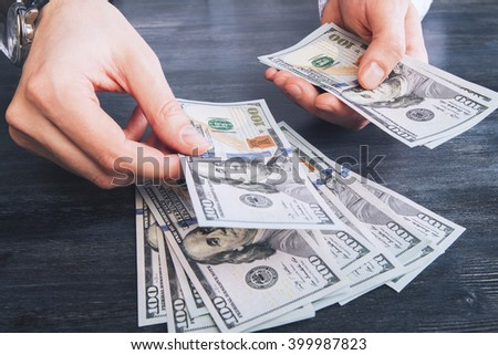 Male hands with watch counting dollar banknotes on dark wooden desktop - stock photo