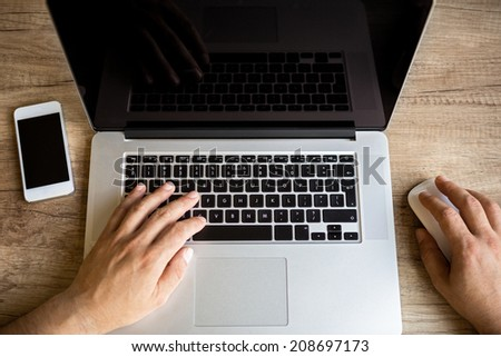 Male hands working on laptop, top view - stock photo