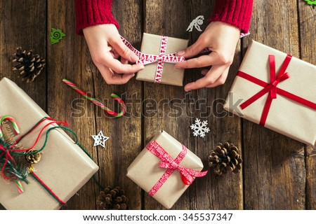 Male hands wrapping xmas gifts into paper and tying them up with red threads - stock photo