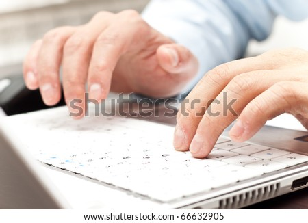 male hands writing on a white laptop - stock photo