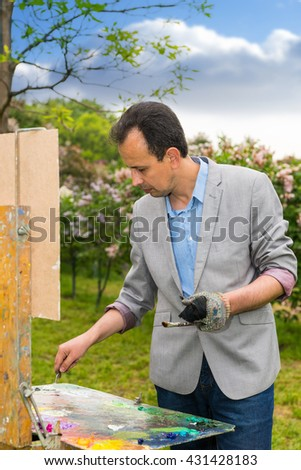 Male handsome middle-aged contemplative artist working  on a trestle and easel painting with oils and acrylics during an art class in a forest - stock photo