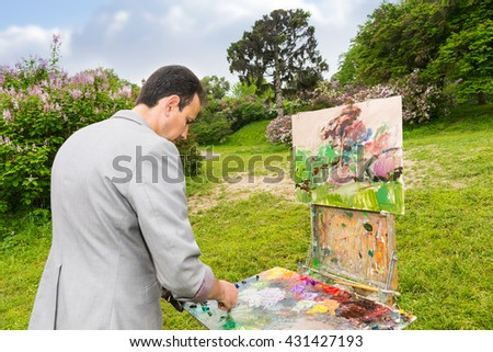 Male handsome middle-aged creative artist mixing paint on a palette standing in front of a sketchbook during an art class in a park - stock photo