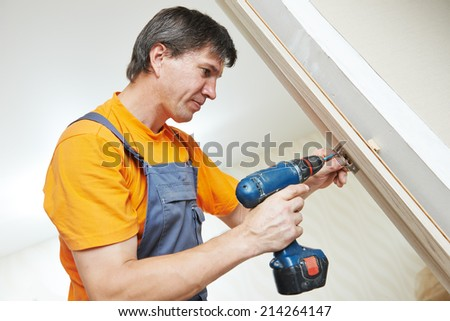 Male handyman carpenter at interior wood door lock installation - stock photo