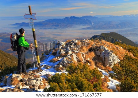 Male hiker at high altitude, on the summit - stock photo