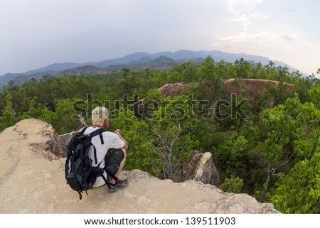 Male hiker in white shirt and backpack looking at view from  canyon edge Resubmit - Reprocessed - stock photo
