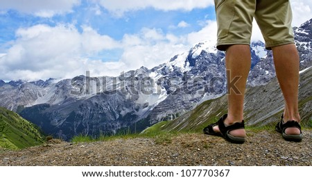Male hiker standing at the top of the mountain - stock photo