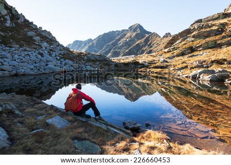 Male hiker takes a rest sitting next a mountain lake. Autumn sunny day. West italian Alps, Oropa, Piemonte, Italy, Europe. - stock photo