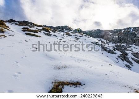 male hiker walks in the snow in the Italian alps - stock photo