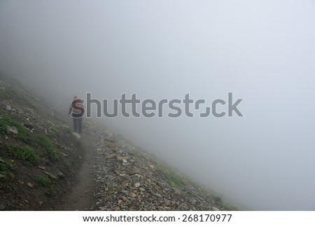 male hiker with a backpack on a highland alpine trail in heavy fog, view from the back - stock photo