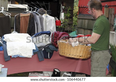 Male holding a basket with linens inside at a yard sale in front of a table with a sleeping bag and clothing items. - stock photo
