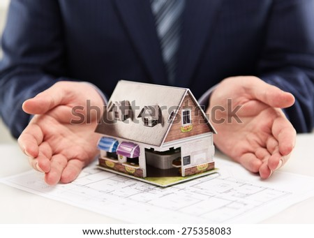 Male house agent showing family residence model to customers. Real estate agreement concept. Shallow depth of field. - stock photo