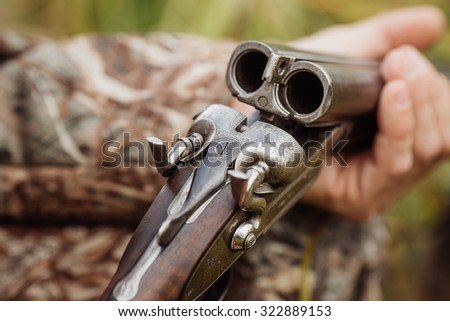 Male hunter in camouflage clothes ready to hunt with hunting rifle - stock photo