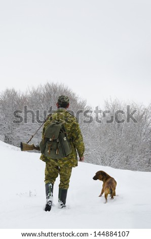 Male hunter in camouflage clothes walking on the snow field with hunting rifle during a hunt, dog follows him, foggy weather - stock photo