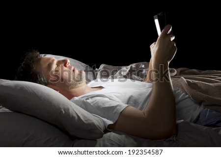 male in bed browsing the internet late at night with a tablet - stock photo