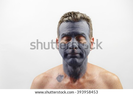 Male in his late forties wearing a charcoal and bentonite clay face mask beauty treatment. Front portrait of a white male wearing a bentonite mud mask beauty treatment. - stock photo