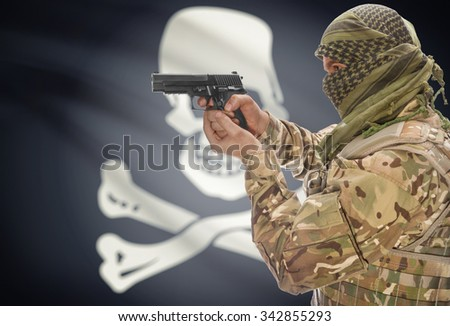 Male in muslim keffiyeh with gun in hand and flag on background series - Jolly Roger - symbol of piracy - stock photo