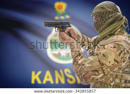 Male in muslim keffiyeh with gun in hand and flag on background series - Kansas - stock photo