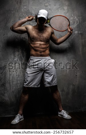 Male in white shorts with tennis racket over grey wall. - stock photo