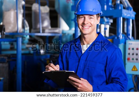 male industrial technician working inside a factory - stock photo