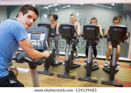 Male instructor at spinning class with four women in gym - stock photo
