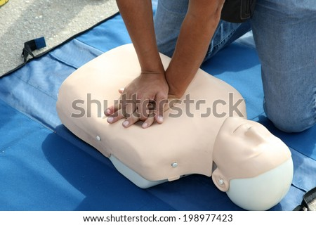 Male instructor showing CPR on training doll - stock photo