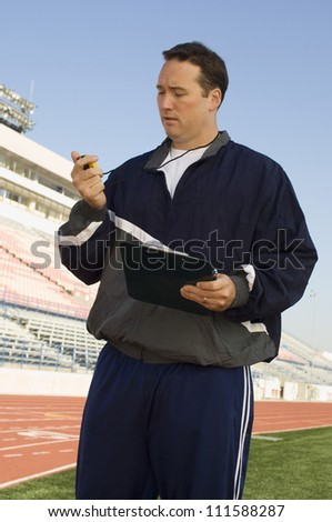 Male instructor with clipboard looking at stopwatch - stock photo
