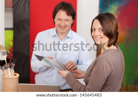 Male interior decorator advising an attractive female customer on paint and carpet colours in his studio - stock photo