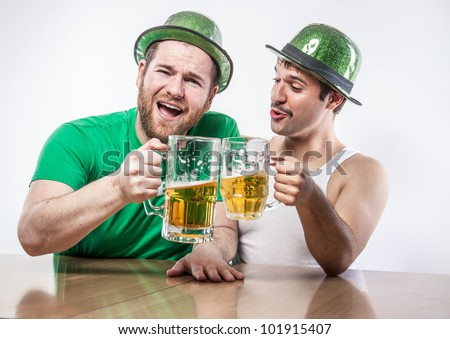 Male Irish friends in green hats toasting on St. Patrick's Day with large mugs of beer at bar tavern - stock photo
