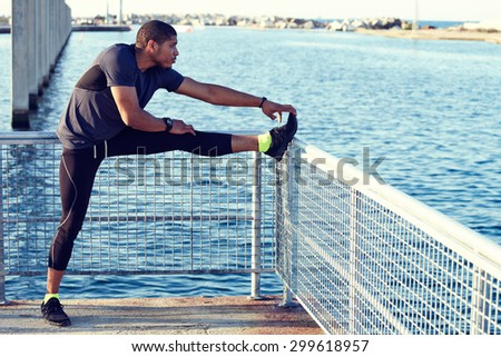 Male jogger doing stretching exercise foreleg or feet muscles above pier fence with copy space area for your text message or information content, muscular build runner preparing for workout outdoors - stock photo