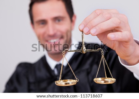 Male Judge Holding The Scale In Courtroom - stock photo