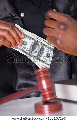 Male Judge Putting Some Money In His Pocket In A Courtroom - stock photo