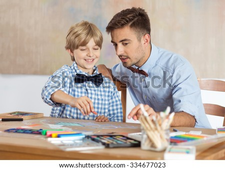 Male kindergarten teacher drawing picture with child - stock photo