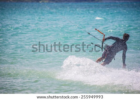 Male kite surfer moving over ocean surface - stock photo