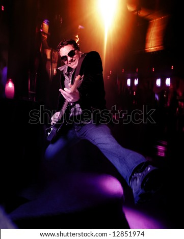 Male lead guitarist with electric guitar jumping on stage - stock photo
