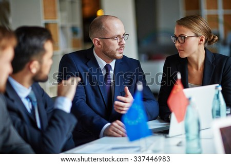 Male leader having a meeting with his colleagues - stock photo