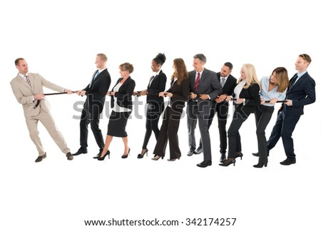 Male leader pulling business team while playing tug of war against white background - stock photo