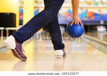 Male legs and bowling ball in alley background - stock photo