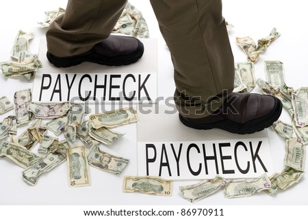 Male legs walking from one paycheck to another with crumpled money scattered about on the floor. - stock photo
