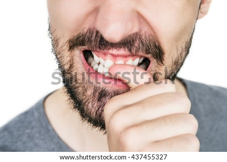 male lips with untrimmed beard at closeup.Close up of male part of face. man bites his nails. Bad habit. - stock photo