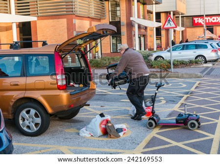 Male loading a disabled persons mobility scooter into the back of a small hatchback car in a shopping centre car park. - stock photo