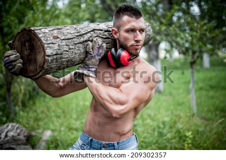 male lumberjack handsome man cutting trees and moving logs around  - stock photo