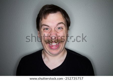 Male making a funny, creepy, weird, over happy smile - stock photo
