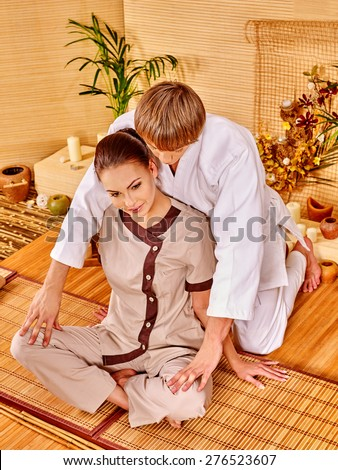 Male masseur doing massage young woman in bamboo spa. Sitting girl. - stock photo
