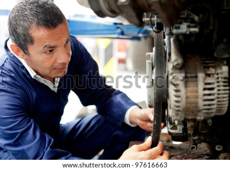 Male mechanic at the garage fixing a car - stock photo