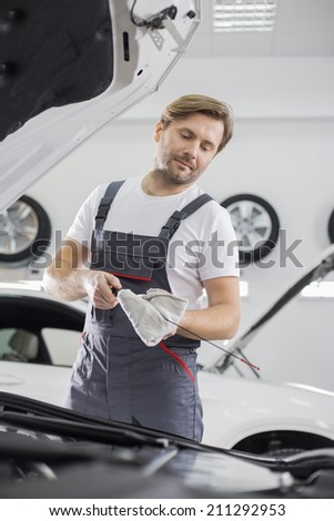 Male mechanic checking oil in car workshop - stock photo