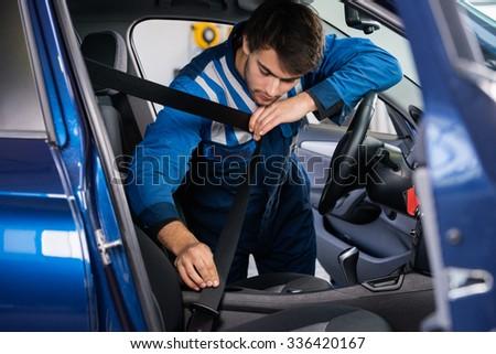 Male mechanic examining car seat belt in garage - stock photo