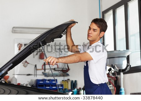 Male mechanic opening car bonnet. Side view - stock photo